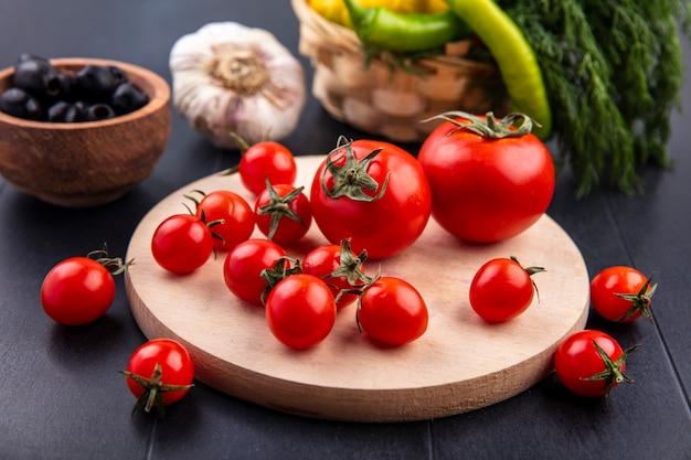 Вид сбоку помидоров на разделочной доске и оливкового чеснока и перца укропа вокруг на черном