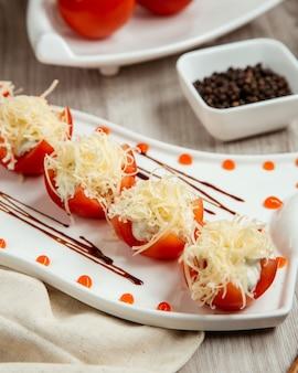 Вид сбоку помидоры, фаршированные сыром на деревянном столе