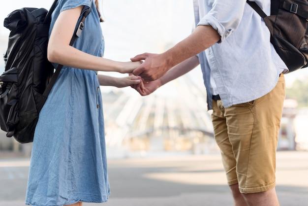 手を繋いでいる観光客カップルの側面図