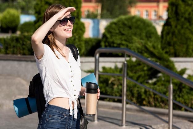 バックパックを持つ観光客女性の側面図