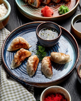 Вид сбоку традиционные азиатские пельмени с мясом и овощами, подается с соевым соусом на тарелку на деревенском