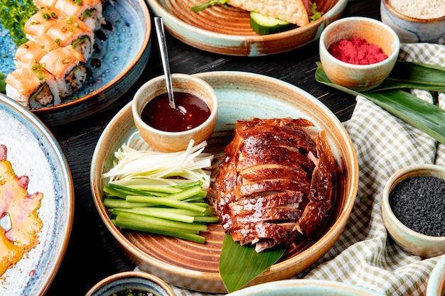 Вид сбоку традиционной азиатской кухни пекинской утки с огурцами и соусом на тарелке