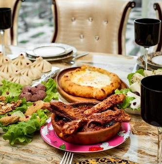木製の大皿にチーズと卵の詰物と伝統的なジョージアン料理ハチャプリプリアジャラの側面図