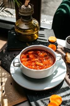 Вид сбоку традиционного русского капустного супа с мясом в миску белого