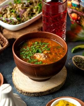 Вид сбоку традиционного русского или украинского красного супа борщ с говядиной и овощной свеклой, картофелем, морковью, капустой, луком, зеленью и специями в глиняной миске на бла