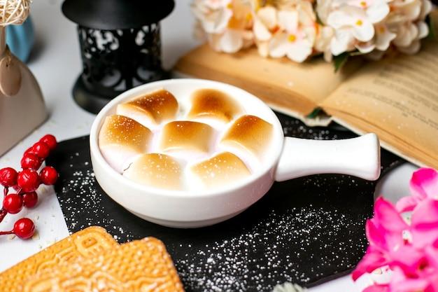 Вид сбоку традиционное блюдо благодарения запеканка из сладкого картофеля с зефиром в порционных формах на деревянной черной разделочной доске