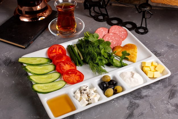 Вид сбоку на традиционный турецкий завтрак с оливками, сыром фета, медом, овощами и чаем