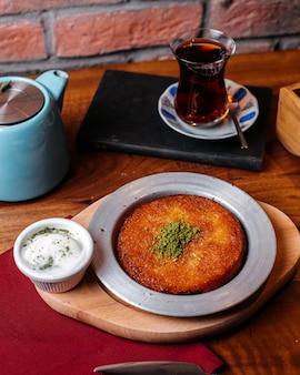 Вид сбоку традиционного турецкого десерта kunefe с фисташковым порошком и сыром на деревянном столе