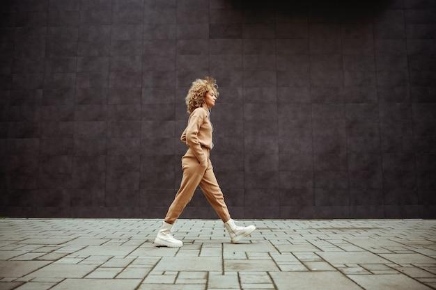 그녀의 주머니에 손을 걷고 음악을 듣고 tracksuit에 트랩 소녀의 측면보기.