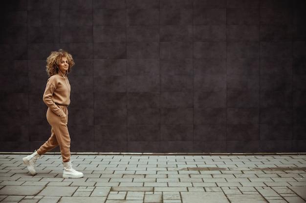 Вид сбоку на девушку-ловушку в спортивном костюме, идущую с руками в карманах и слушающей музыку.