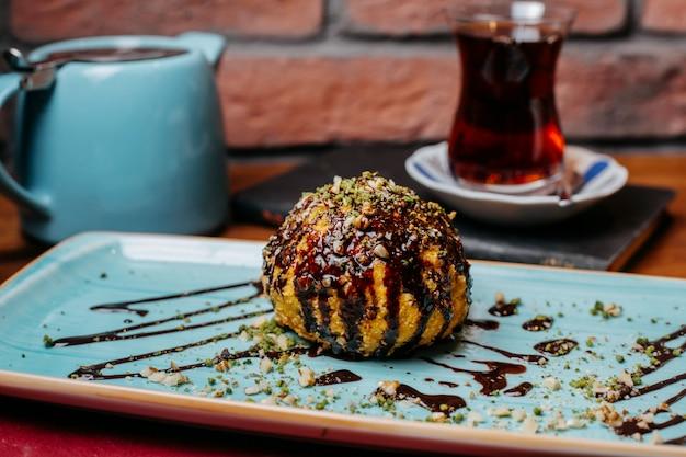 Вид сбоку турецкого десерта жареного мороженого, покрытого шоколадным сиропом на столе