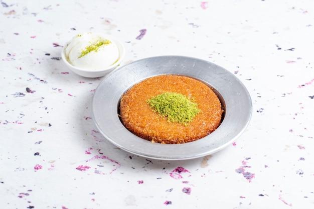 Вид сбоку турецкого традиционного десерта kunefe подается с мороженым на столе
