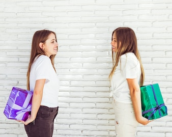 Side view of two beautiful women hiding gift from each other