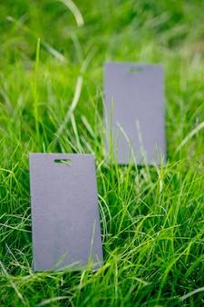 Вид сбоку двух черных ценников на одежду, креативный макет лужайки зеленой травы с биркой с логотипом.