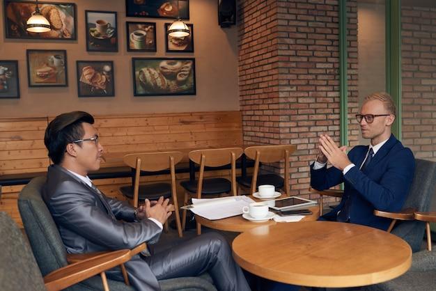 Вид сбоку двух бизнесменов, сидящих в кафе, обсуждающих груды документации