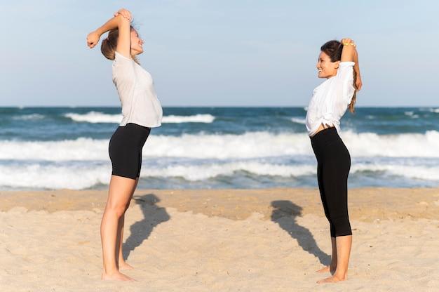 ビーチで運動している2人の女性の友人の側面図