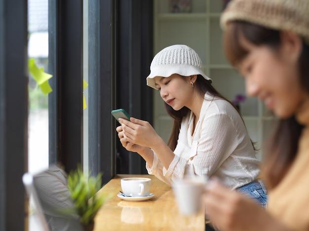 Вид сбоку двух девочек-подростков, использующих смартфон и пьющих кофе в кафе