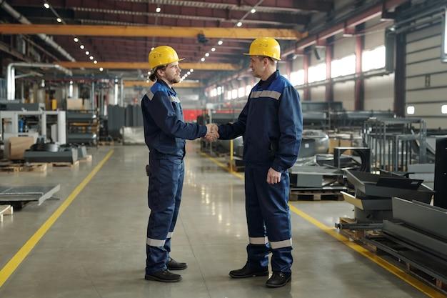 작업장에서 아침에 악수를 하며 서로 인사하는 보호용 안전모와 작업복을 입은 두 남성 엔지니어의 측면