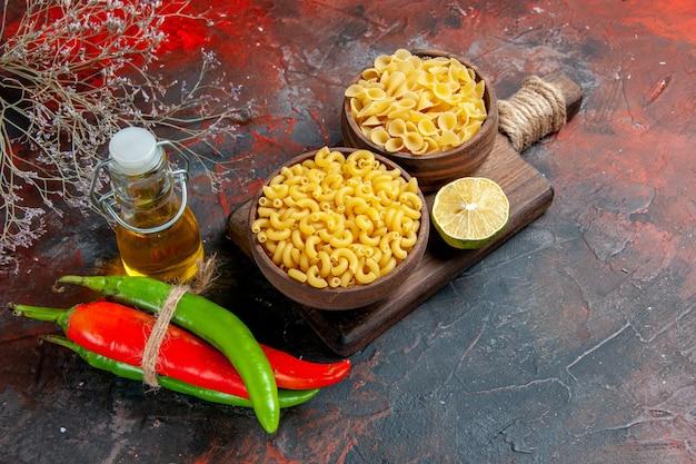 Вид сбоку сырых макарон на разделочной доске кайенский перец, связанный друг с другом веревкой, масло, лимон, чеснок, на столе смешанных цветов