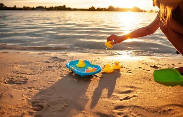 해변에 서서 작은 수영장에서 노란색 고무 오리를 가지고 노는 알아볼 수 없는 소녀의 측면