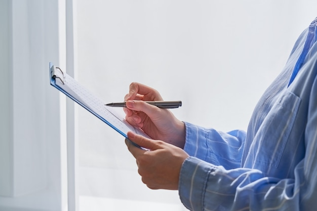 클립보드에 펜으로 메모를 하는 형식적인 옷을 입은 알아볼 수 없는 여성의 측면