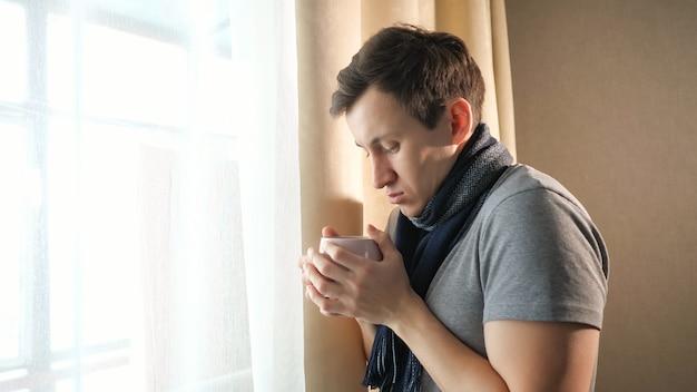 自宅の窓の近くに立っている間芳香族の熱い飲み物のカップを保持しているスカーフで体調不良の男性の側面図