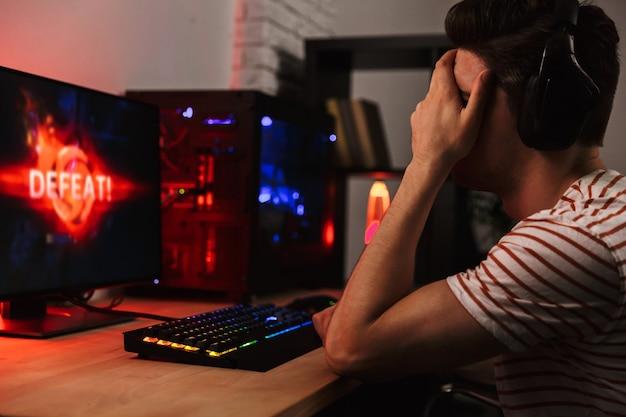 Расстроенный геймер, играющий в видеоигры на компьютере, вид сбоку