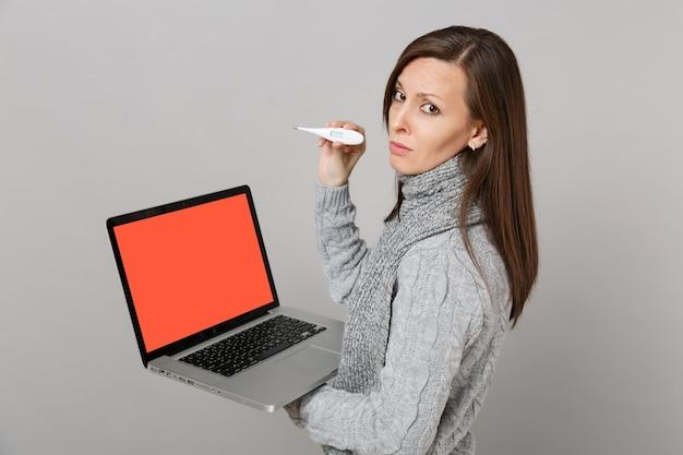 灰色の背景に分離された空白の空の画面で温度計ラップトップpcコンピューターを保持しているセータースカーフで動揺した女性の側面図。寒い季節のコンセプトをコンサルティングする健康的なライフスタイルのオンライン治療。