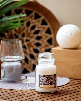 木製のテーブルにガラスのバニラの香りのキャンドルの側面図