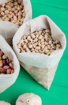 녹색 나무 표면에 자루에 줄 지어 콩의 다양한 유형의 측면보기
