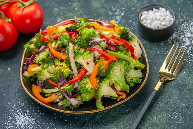 暗い背景に茎を持つさまざまな野菜とフォークトマトとプレートのビーガンサラダの側面図