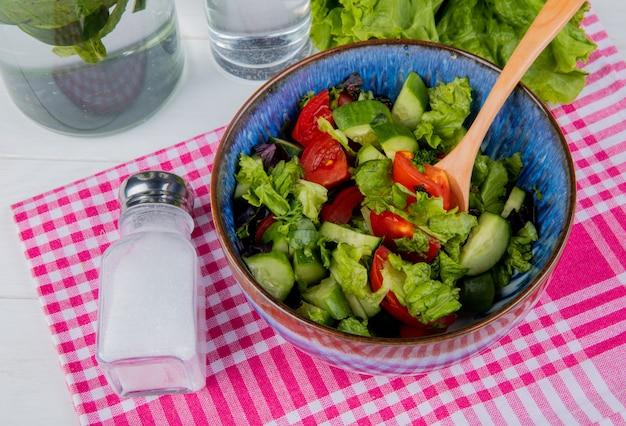 Вид сбоку овощного салата и соли на клетчатой ткани с детокс воды и салата на деревянный стол