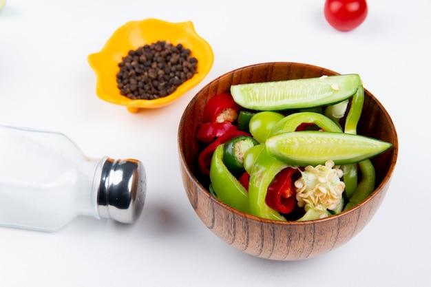 Вид сбоку овощного салата в миску и соль с семенами черного перца на белом столе