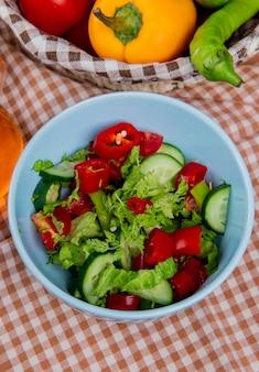 Вид сбоку овощного салата в миске с овощами в корзине на клетчатой ткани