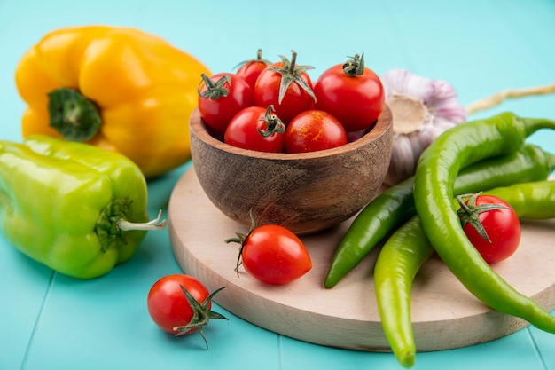 Вид сбоку овощей как миска томатно-чесночного перца на разделочной доске на синем
