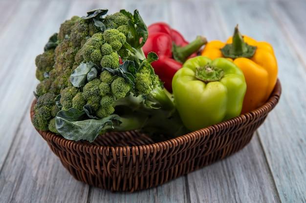 木製の背景にバスケットにブロッコリーとピーマンとして野菜の側面図