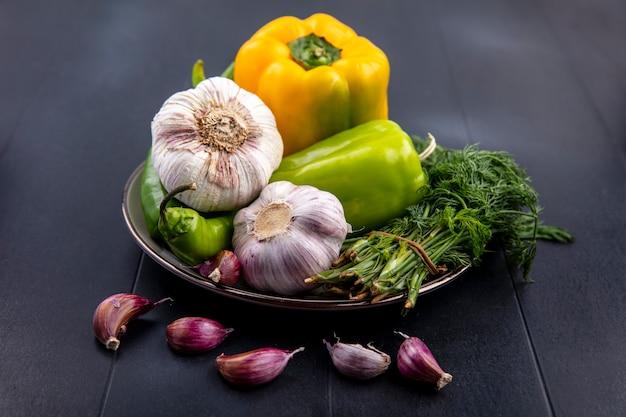 Вид сбоку овощей как чесночный перец, укроп в тарелке с зубчиками чеснока на черном
