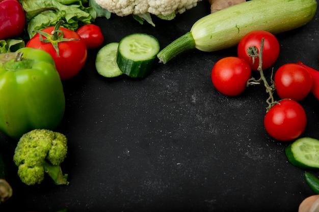 コピースペースと黒の背景にペッパーキュウリトマトズッキーニなどの野菜の側面図