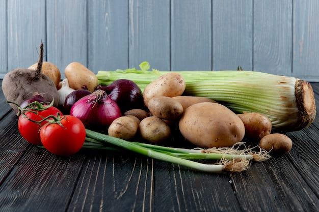 木製の表面とコピースペースと背景にネギトマトビート根タマネギとセロリとして野菜の側面図