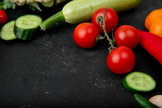 コピースペースと黒の背景にトマトキュウリズッキーニとして野菜の側面図