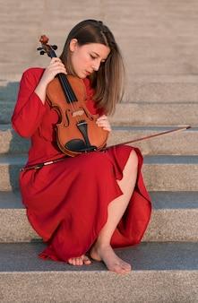 Вид сбоку скрипача на ступеньках