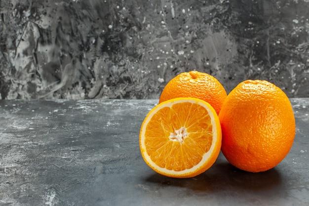 회색 배경에 비타민 소스 컷 및 전체 신선한 오렌지의 측면 보기