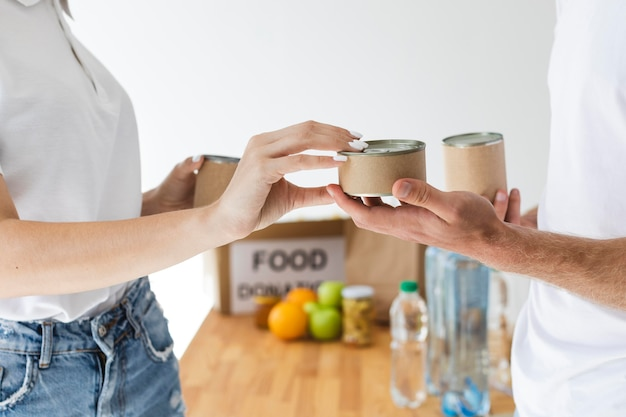 Вид сбоку на добровольцев, обменивающих банки на коробки для пожертвований еды