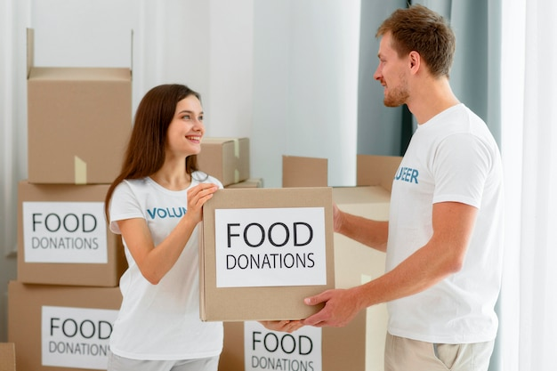 음식 기부 상자를 처리하는 자원 봉사자의 측면보기