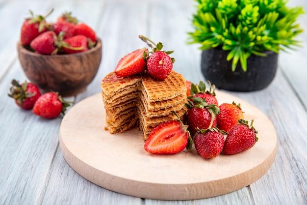 Вид сбоку вафельного печенья на разделочной доске и клубники в миске и на дереве