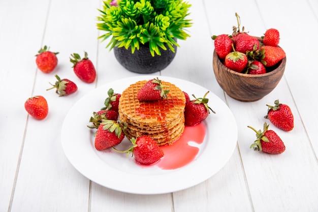 Вид сбоку вафельного печенья с клубникой в тарелке и в миске с цветком на дереве