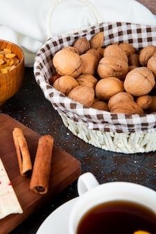 Вид сбоку грецких орехов в плетеной корзине и палочки корицы на деревенском