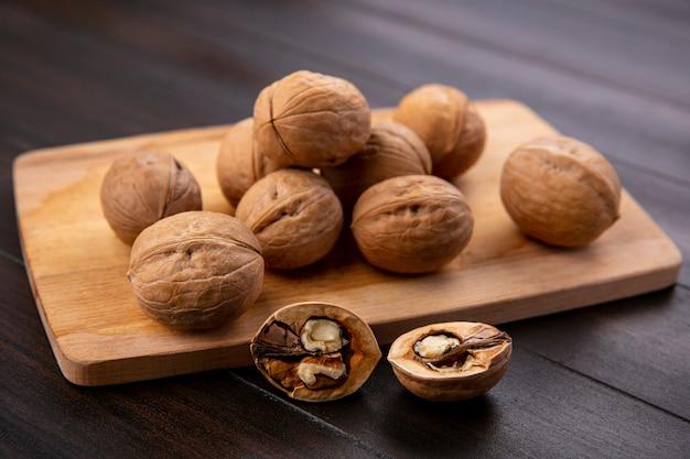 Вид сбоку грецких орехов на доске на деревянной поверхности