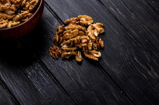 Вид сбоку грецких орехов, разбросанных на деревенском