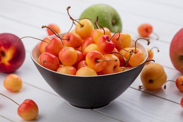 Вид сбоку белой вишни в миске с яблоками на белой поверхности